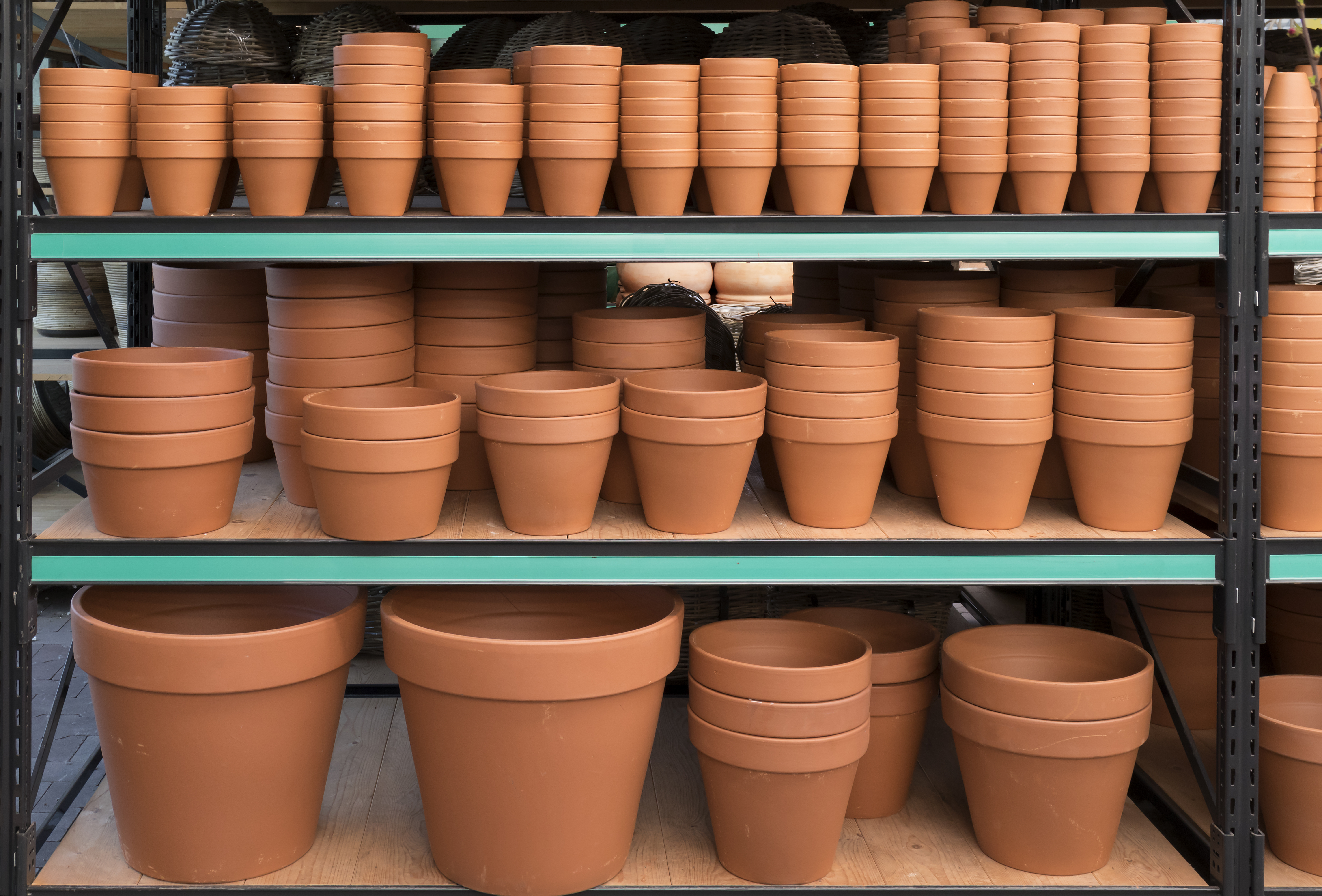 Shelves of different sized tan pots.